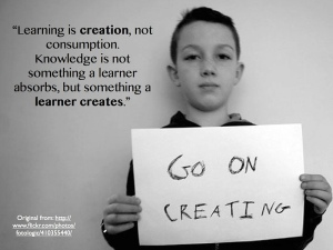 An image showing a boy holding a poster saying 'Go On Creating'